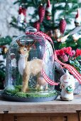 Christmas arrangement - animal ornament under bell jar and angel figurine on wooden table top in front of decorated Christmas tree