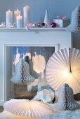 Circular paper lampshades and decorative paper bells arranged around fireplace with lit candles on mantelpiece