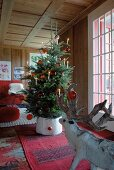 Christmas tree decorated with candles and red glass baubles in room with wooden walls