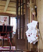 Hand-sewn parcels hanging from willow besom broom as Advent calendar