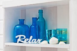 Blue ornamental bottles and glasses on white shelf