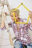 Renovierungsarbeiten - Frau sitzt auf der Leiter und hält einen Meterstab in der Hand