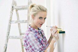 Renovierungsarbeiten - Frau mit Wasserwaage und Stift