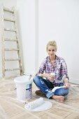 renovierungsarbeiten frau bohrt loch in die wand bild kaufen living4media. Black Bedroom Furniture Sets. Home Design Ideas