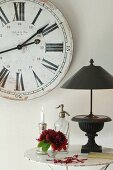 Black table lamp with Ancient Greek style base in front of vintage wall clock