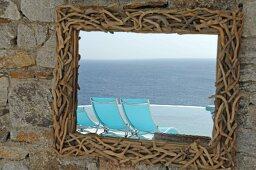 Spiegel mit Rahmen aus kleinen Zweigen und sich spiegelnde Liegestühle am Meer