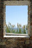 Blick durch Fensteröffnung in Natursteinmauer auf das Meer