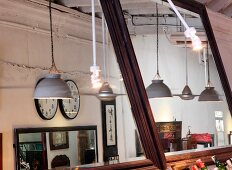 Pendant lamps with metal lampshades and clocks on wall of restaurant interior reflected in two large wall mirrors
