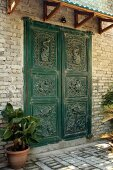 Green-painted, carved front door and small porch on brick facade