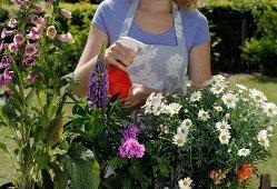 Woman in garden watering plants