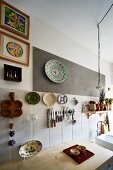Knives and scissors on magnetic rack surrounded by colourful collectors' plates on mixture of wall tiles above improvised kitchen counter