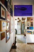 Anteroom with crowded gallery of pictures and violet poster with lettering above doorway leading to improvised kitchen