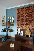 Antique collectors' items and large, decorative kilim on pale blue living room wall