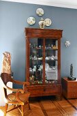 Chinese vase, decorative wall plates and collection of china in antique display cabinet against wall painted light blue