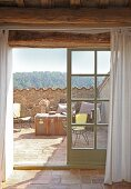 View through French windows onto Mediterranean roof terrace with wire furniture and travelling trunk used as table