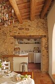 View of stone wall and doorway leading to simple, white kitchen from dining area with Spanish chandelier