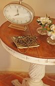 Old-fashioned table clock and bead necklace in dish on vintage-effect Mediterranean side table