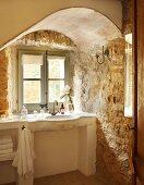 Craggy charm - masonry washstand in window niche with rough stone walls