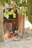 Bicycle with basket in front of open door of stone house; woman with leather suitcases waiting on stairs