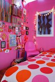 Mädchenzimmer mit rosa Wänden, bunter Wanddekoration und Lichterkette
