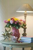 Bunch of flowers, table lamp, decorative star and books on table