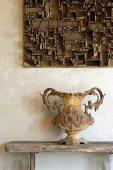Antike, gusseiserne Vase mit Fuss auf rustikaler Holzbank und Setzkasten-Holzobjekt an Wand
