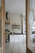 Blick durch offene Tür in schlichte Landhausküche mit weißem Fliesenboden und dunklen Einlegerfliesen