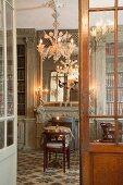 Blick durch offene Tür in Bibliothek mit rundem Tisch und Stuhl vor Kamin unter floralem Kronleuchter