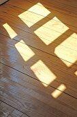 Sun shining through window on wooden floor