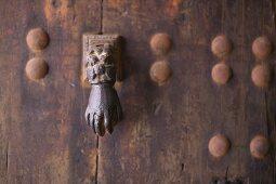 Door knocker in the shape of a hand on rusty metal door