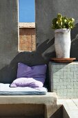 Cushions on masonry bench and potted plant on shelf next to window-like opening in wall