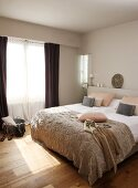Modern double bed with pale brown bedspread in simple bedroom