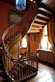 Traditionelles Treppenhaus mit gewendelter Holztreppe vor rotbrauner Wand und alter Dielenboden