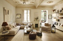 Generous corner sofa and floating shelving in simple, modern living room in period apartment below immaculate stucco ceiling