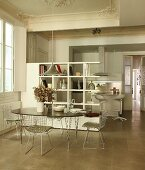 Dining table and 50s and 60s classic designer furniture in stylish period apartment with stucco ceiling; partition screening modern, open-plan kitchen