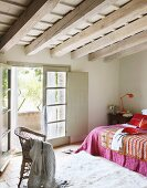 Attic bedroom - wicker chair on flokati rug and colourful bedspread on bed next to open balcony door