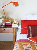 Red retro table lamp on bedside table next to bed with red scatter cushions and bedspread