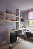 Modern work area with white fitted shelving above desk in teenager's room with lilac walls