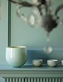 Elegant china bowl and tiny dishes on mantelpiece in front of profiled wooden wall panel