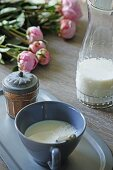 Cup and glass carafe of milk, spice jar and peonies on wooden table