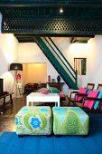 Elegante Sitzpolster und weisser Tisch in modernem Wohnzimmer mit traditioneller Treppe aus Holz