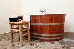 Rustikaler Hocker vor Holzzuber-Badewanne in schlichter Badezimmerecke