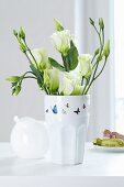 Butterfly-patterned tape on vase of white Texas bluebells (Eustoma grandiflorum)