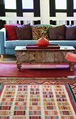 Colourful rug in front of onion-shaped vase on vintage coffee table and blue sofa with patterned cushions