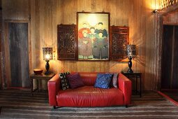 Red leather couch flanked by two side tables against plain wooden wall and below family portrait and carved wooden cabinets