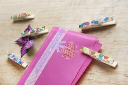 A hand-decorated envelope and decorated wooden clothes pegs