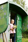 Blonde girl with bouquet in summer house