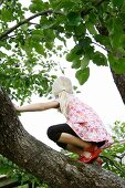 Blonde girl climbing a tree