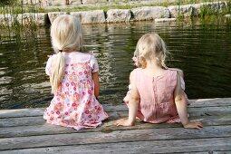 Two blonde girls sitting next to a garden pond