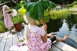 Two blonde girls next to garden pond
